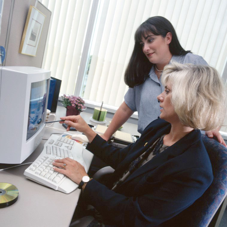 Office workers using older computers in the 1990s.